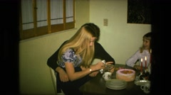 1974: woman sitting together with her family at table on her birthday opening Stock Footage