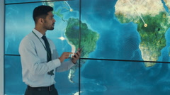 4K Businessman with tablet looking at large world map graphic on video wall Stock Footage