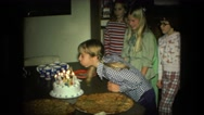 1974: cute young girl with pigtails blowing out birthday candles on cake  Stock Footage