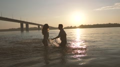 Happy couple in love playing in the river, hugging and kissing each other Stock Footage