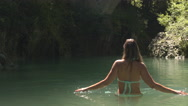 AERIAL, CLOSE UP: Beautiful smiling girl in bikini standing waist high in water Stock Footage