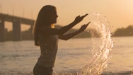 Beautiful couple splashing each other in the river on a sunset Stock Footage