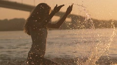 Playful couple in love playing with water in the river on sunset Stock Footage