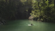 AERIAL, CLOSE UP: Young girl swimming in refreshing Soca river on sunny day Stock Footage