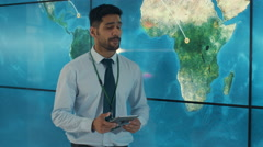 4K Businessman with tablet giving a presentation in front of large world map Stock Footage