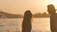 Portrait of young couple splashing each other in the sun rays Stock Footage