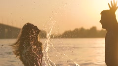 Young pair playing in water on sunset Stock Footage