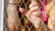 Teenager girl is sad angry unhappy disappointed holding wire netting in stadium Stock Footage