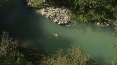 AERIAL: Young woman swimming frog style technique in green river in wilderness Stock Footage