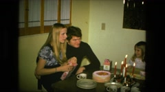 1974: happy birthday mom family sitting dinner table gift birthday party  Stock Footage