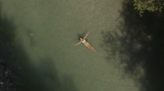AERIAL: Beautiful young woman doing starfish float in refreshing emerald river Stock Footage