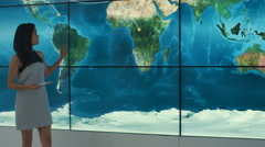 4K Businesswoman with tablet giving a presentation in front of large world map Stock Footage