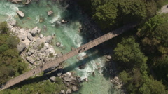 AERIAL: Flying above wooden rope bridge leading above raging fast river rapids Stock Footage