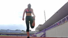 Low angle shot of teenager girl athlete stretching before running on a stadium Stock Footage