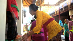 Bali - Balinese wedding guests in traditional dress preparing gifts Stock Footage