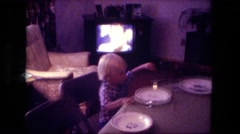 1974: blonde caucasian boy watching tv eating lunch at kitchen counter table Stock Footage