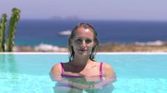 Blonde model goes underwater in pool with blue ocean background 4K Stock Footage