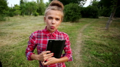 Girl with tablet pc blew up bubble from chewing gum Stock Footage