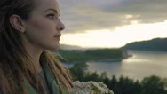 Young Woman Stands On Mountain Top, She Smells Flowers, Takes In Views Of River Stock Footage