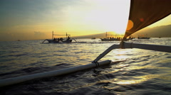 Balinese catamaran craft with tourists enjoying a tropical sunrise while dolphin Stock Footage