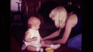 1974: mom is collecting mess from little girl FORT WAYNE, INDIANA Stock Footage