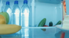 Young man opens the fridge and choosing something to eat and takes salad Stock Footage
