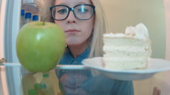 Young woman opens the fridge choosing between an apple and cake and chooses cake Stock Footage