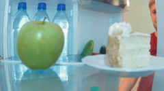 Young man opens the fridge choosing between an apple and cake and chooses cake Stock Footage