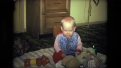 1974: happy child sits on blanket surrounded by many toys tries to decide which Stock Footage