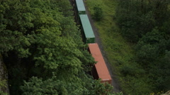 Aerial View Of Freight Train Passing Through Lush Forest Stock Footage