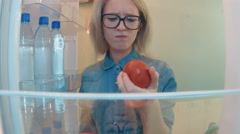 Young woman opens the fridge want to eat but finds only one tomato and Stock Footage