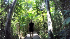 Female walking through woodland Boardwalk with palm trees  Stock Footage