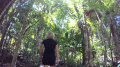Female walking through tropical woodland trees and lush green vegetation  Stock Footage