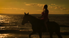 A beautiful blonde young sexy woman in a red dress riding a horse at a lake Stock Footage