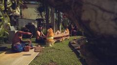 Balinese men playing gamelan, wood carving and painting in resort near pool Stock Footage