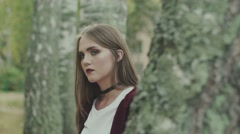 Portrait of a young model in the forest. Maroon sweater and bright lips Stock Footage