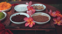 Spa powders in small bowls on wooden table with frangipani, slider Stock Footage