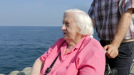 Senior woman in a wheelchair is looking at sea Stock Footage