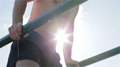 Slow motion. The young strong man is pushing up on the parallel bars. Stock Footage