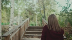 Young girl climbs the stairs in the forest. Maroon cardigan. Walk alone Stock Footage