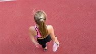 Top view of teenager girl athlete stretching before running on a stadium Stock Footage