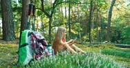 Hiker girl child 8-9 years using cell phone and sitting in the grass in forest Stock Footage