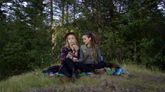 Young Women Enjoy A Picnic In A Field, One Uses Her Smartphone To Take Selfies Stock Footage
