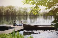 Couple relaxing on dock at sunny lakeside near canoe Stock Photos
