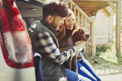Couple petting pet dog at back of car Stock Photos