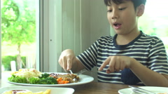 Little Asian boy eating steak with vegetable Salad at restaurant with smile face Stock Footage