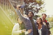 Smiling friends with camera phone taking selfie outdoors Stock Photos