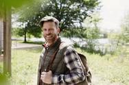 Portrait smiling hiker with backpack in sunny woods Stock Photos