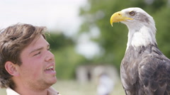 4K Worker at a conservation centre holding a bald eagle & talking to visitors Stock Footage