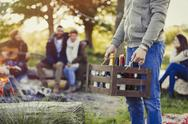 Man carrying crate of wine and beer at campsite with friends Stock Photos